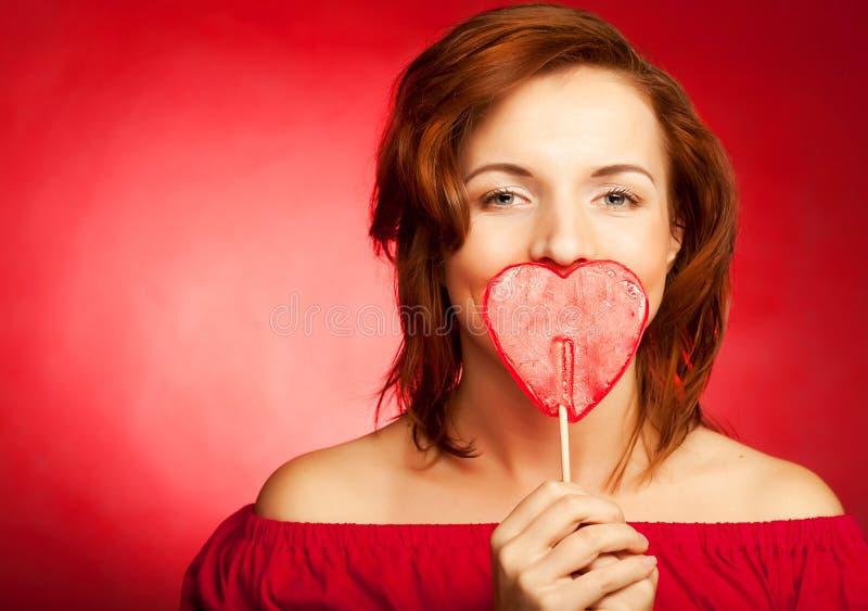 Glückliche Frau mit Innersüßigkeit-Lutschbonbonknall stockfotos