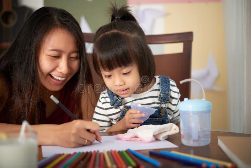 Glückliche Frau mit kleinem Mädchen zu Hause stockbilder