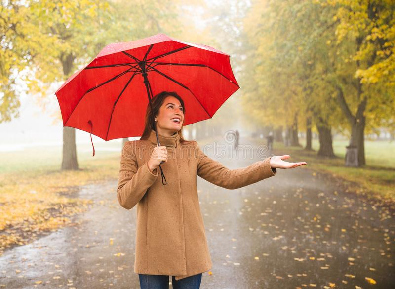 Glückliche Frau mit rotem Regenschirm gehend am Regen im schönen Herbstpark stockfoto