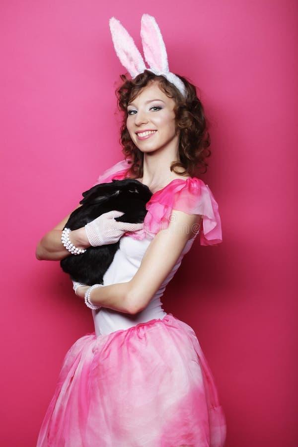 Glückliche Frau mit schwarzem Kaninchen lizenzfreie stockbilder