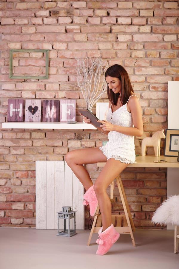 Glückliche Frau mit Tablette zu Hause stockfotos