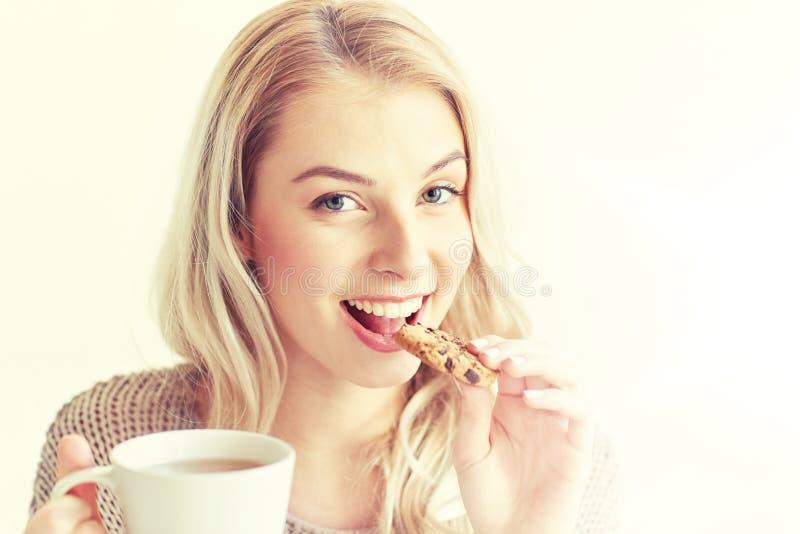 Glückliche Frau mit Tee Plätzchen zu Hause essend stockfotos