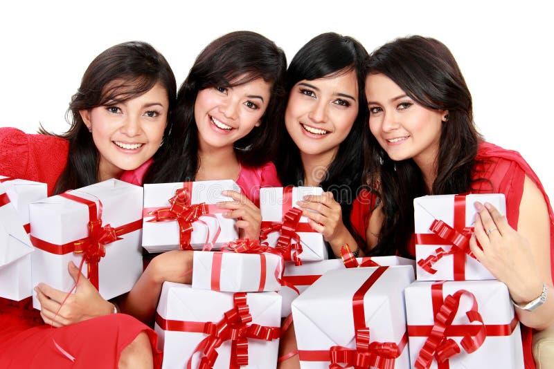 Glückliche Frau mit vier Asiaten mit Weihnachts-Sankt-Hut, der Geschenkbox hält stockfotos