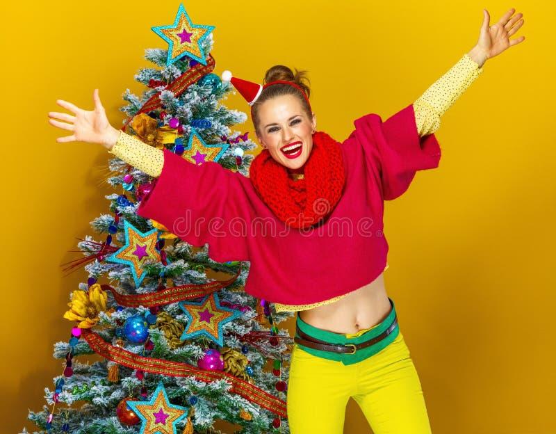 Glückliche Frau nahe Weihnachtsbaum auf gelbem Hintergrund freuend lizenzfreie stockfotos