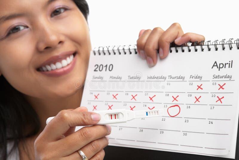 Glückliche Frau, positive Schwangerschaftprüfung u. Kalender lizenzfreies stockbild