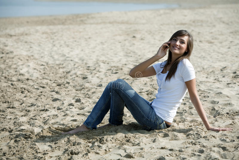 Glückliche Frau sitzen im Sand mit einem Handy lizenzfreie stockfotografie