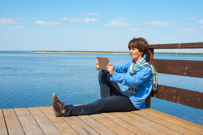 Glückliche Frau sitzt auf einem hölzernen Pier mit Tablette stockbilder