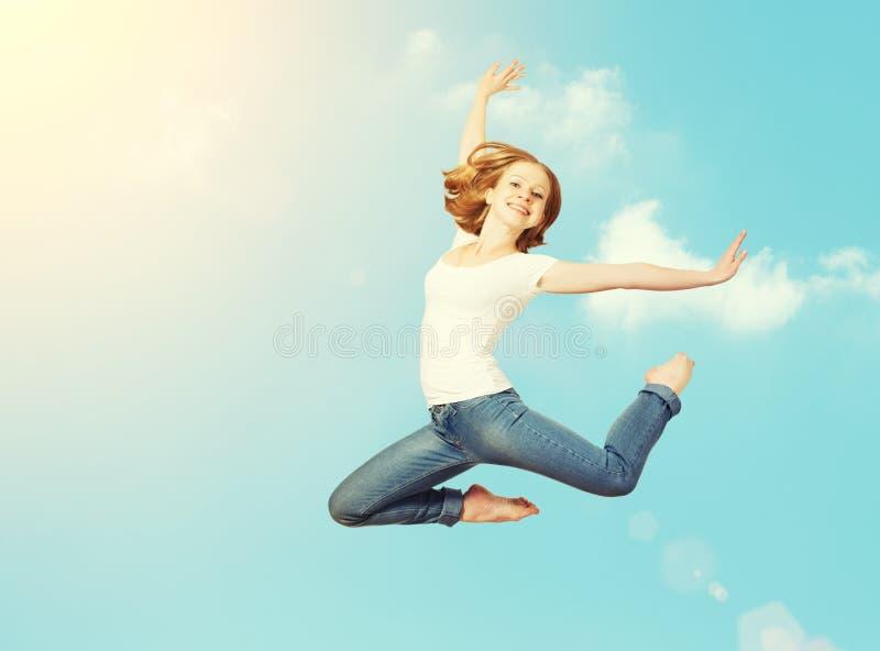 Glückliche Frau springen in den Himmel lizenzfreie stockfotos