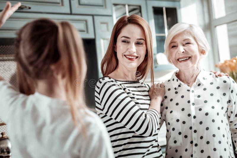 Glückliche Frau und ihre ältere Mutter, die das Mädchen und das Lächeln betrachtet stockfotografie