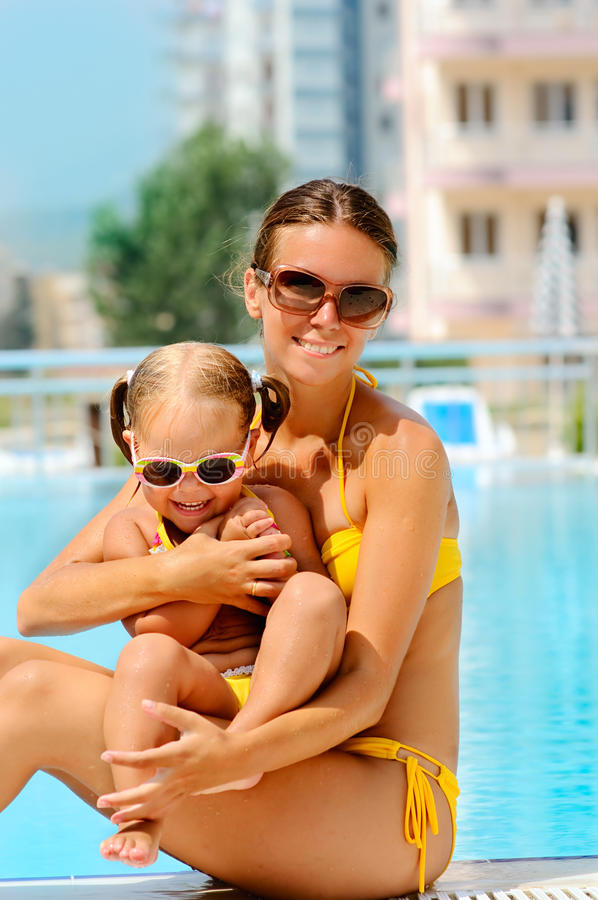 Glückliche Frau und ihre Tochter nahe Pool stockfoto
