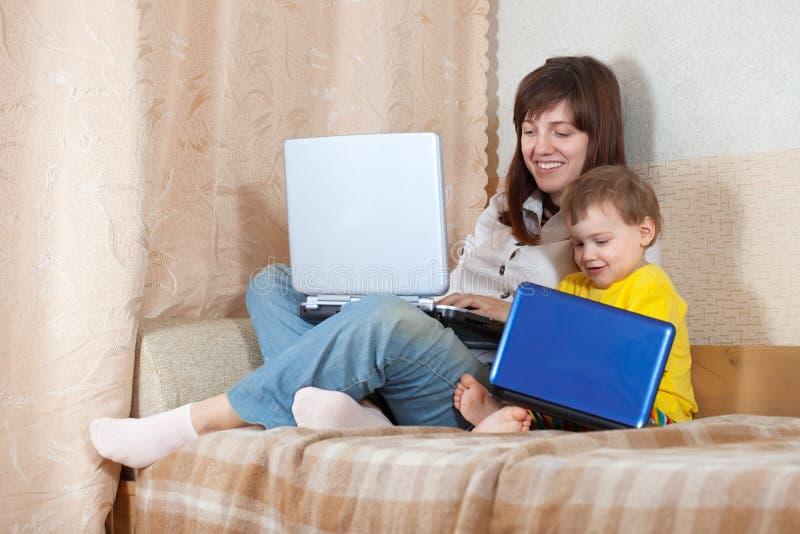 Glückliche Frau und Kind mit Laptopen stockfoto