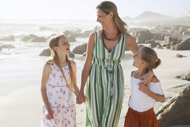 Glückliche Frau und Töchter, die am Strand in Verbindung stehen lizenzfreie stockfotos
