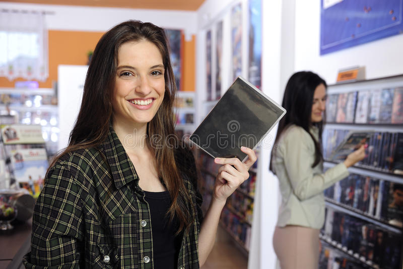 Glückliche Frau am video Mietspeicher stockfotos