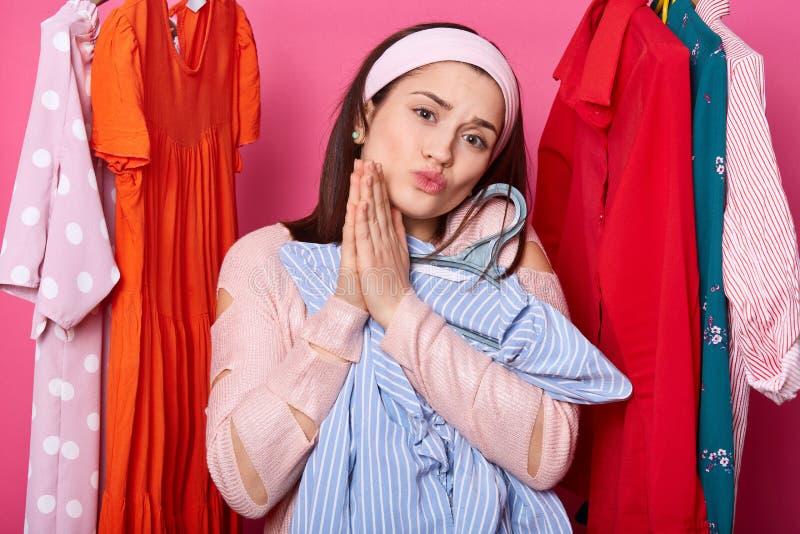 Glückliche Frau wählt Kleid Brunette Mädchen trägt rosafarbene Kleidung, betet für etwas, hält Lippen gerundet, umfasst Neuanscha stockfoto