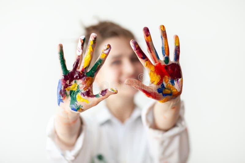 Glückliche Frau, welche die Hände gemalt in den bunten Farben zeigt stockbilder