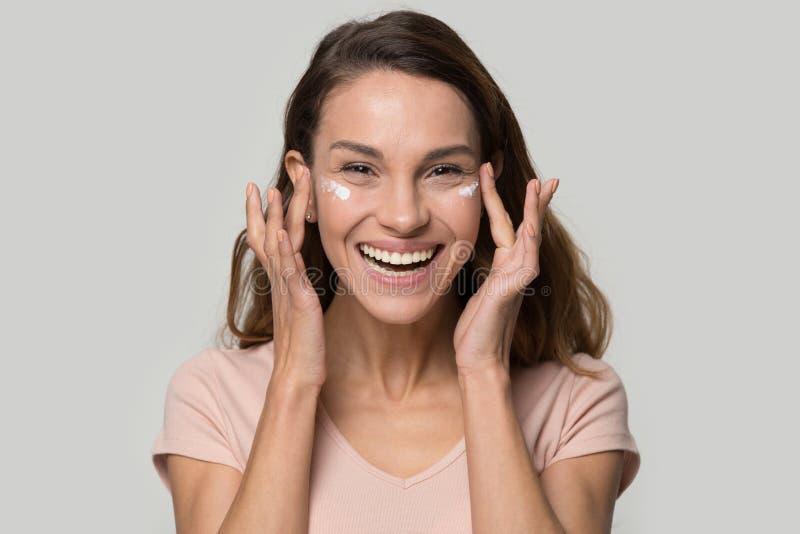 Glückliche Frau, welche die Kamera aufträgt Augenlidfeuchtigkeitscreme betrachtet stockfotografie