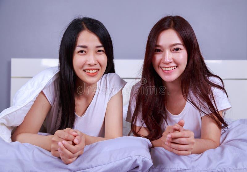 Glückliche Frau zwei, die auf Bett im Schlafzimmer liegt lizenzfreies stockbild