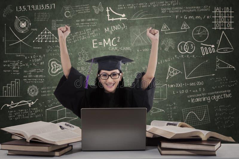 Glückliche Frauabsolvent-Erhöhungshände In Der Klasse Lizenzfreie Stockfotos