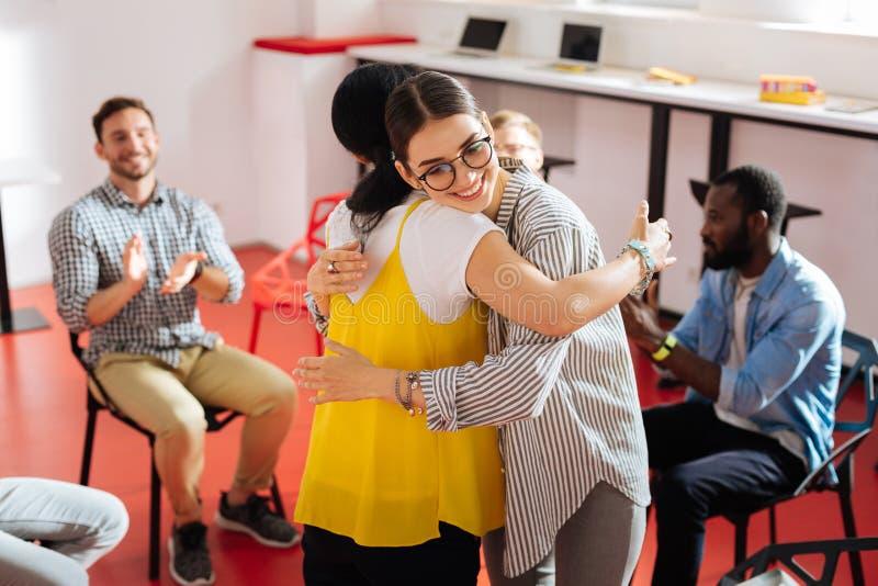 Glückliche Frauen, die an der psychologischen Sitzung lächeln und umarmen stockfotografie