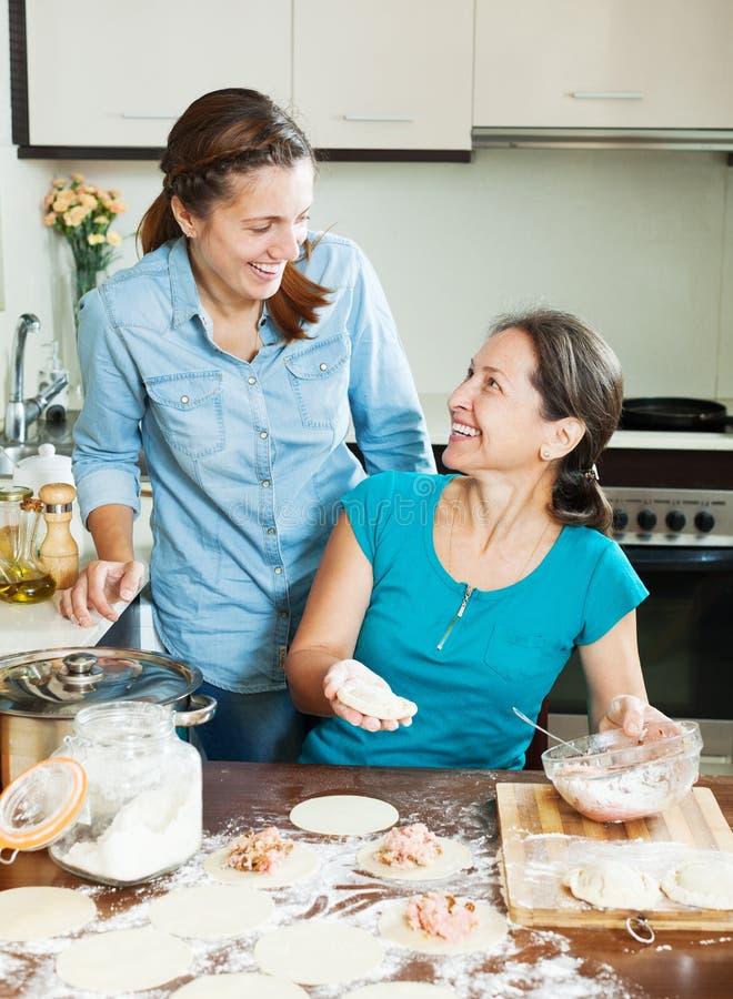 Glückliche Frauen, die Fleischtorten machen stockfoto