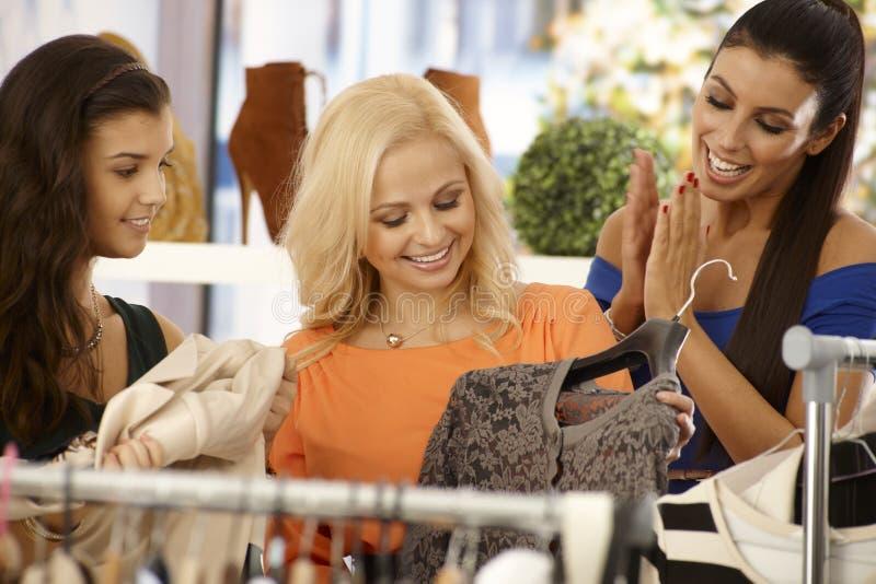 Glückliche Frauen, die am Kleidungsspeicher kaufen stockfotos