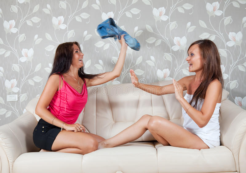 Glückliche Frauen, die mit Kleidung kämpfen lizenzfreie stockfotos