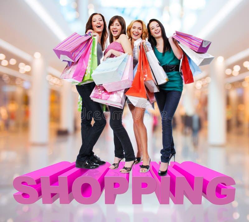 Glückliche Frauen mit Einkaufstaschen am Speicher lizenzfreies stockfoto