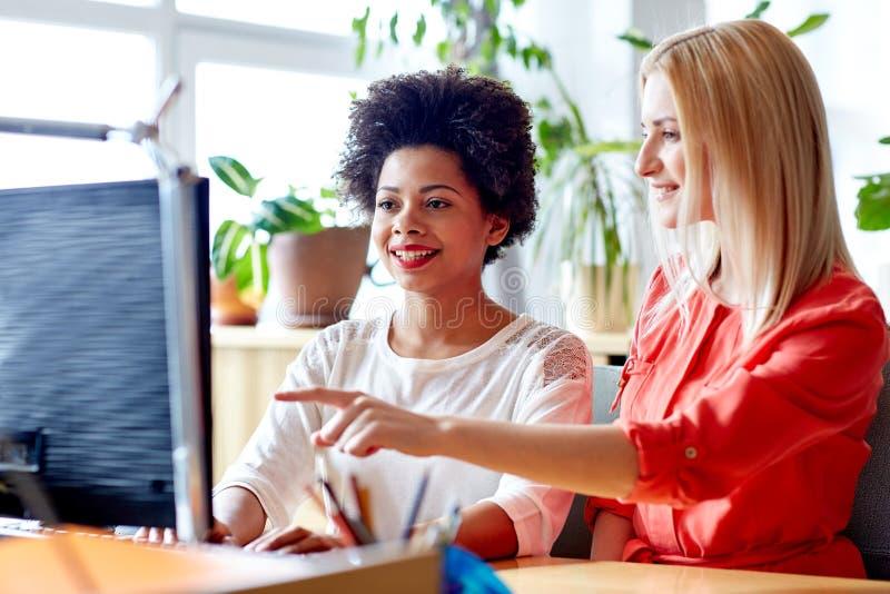 Glückliche Frauen oder Studenten mit Computer im Büro lizenzfreie stockfotos