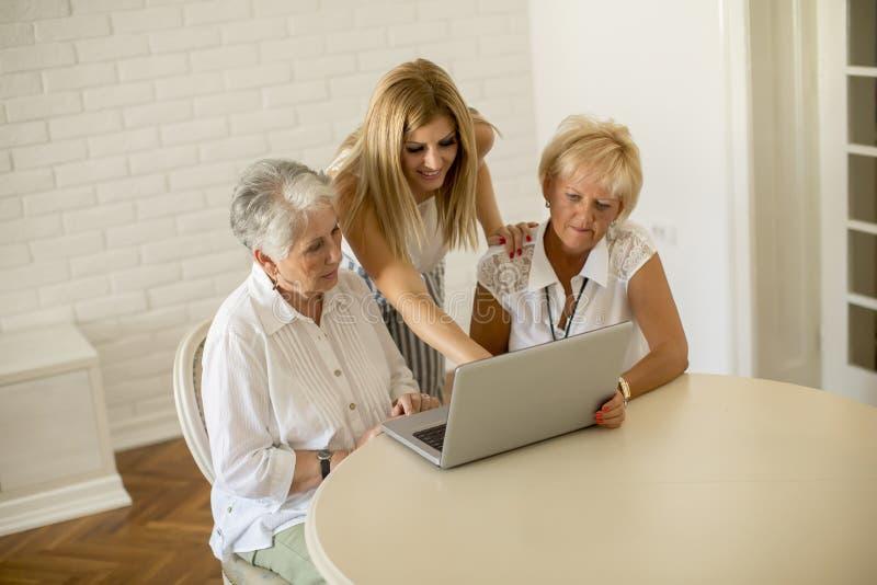 Glückliche Frauen von drei Generationen unter Verwendung des Laptops im Raum zu Hause stockfotos