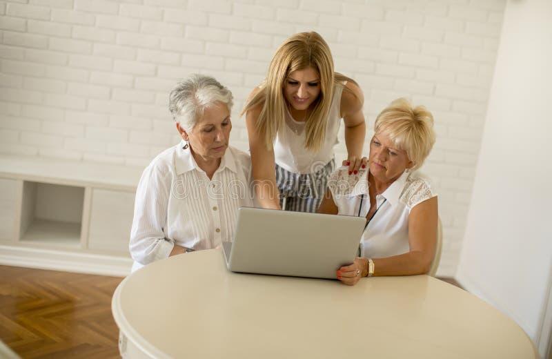 Glückliche Frauen von drei Generationen unter Verwendung des Laptops im Raum zu Hause stockbilder