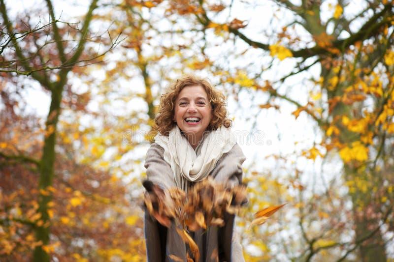 Glückliche Frauen-werfende Blätter lizenzfreies stockfoto