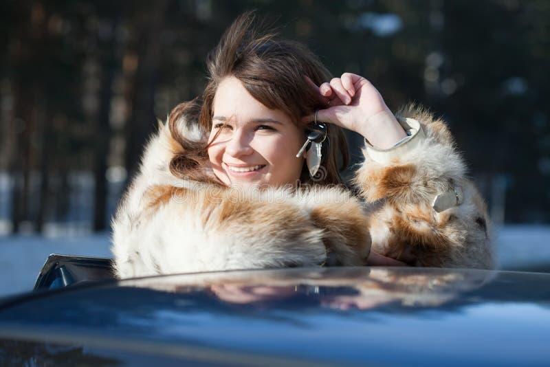 Glückliche Frauenholding-Autotasten lizenzfreie stockbilder