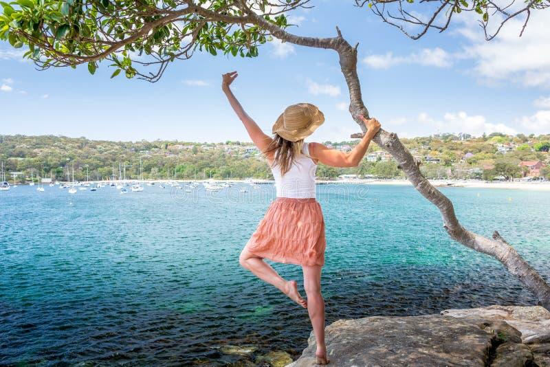 Glückliche Frauentanzpirouette neben Baum durch den Ozean lizenzfreies stockfoto