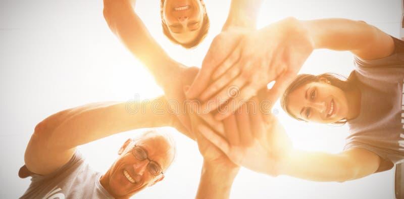 Glückliche Freiwillige, die zusammen Hände stapeln lizenzfreie stockfotos