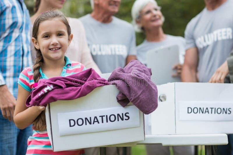 Glückliche freiwillige Familie, die Spendenkästen hält stockfotos
