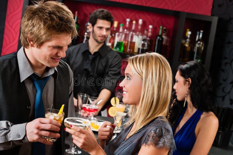 Glückliche Freunde am Cocktailstab genießen Getränke stockfotos