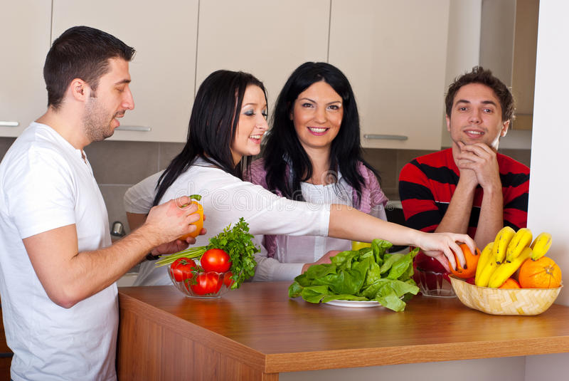 Glückliche Freunde in der Küche mit Gemüse lizenzfreie stockfotos