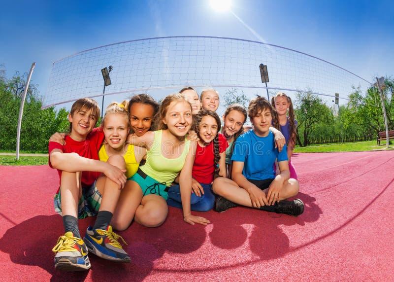 Glückliche Freunde, die auf dem Volleyballspielgericht sitzen stockfotografie