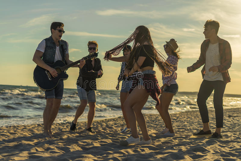 Glückliche Freunde, die auf den Strand tanzen Männer spielt Gitarre lizenzfreies stockfoto