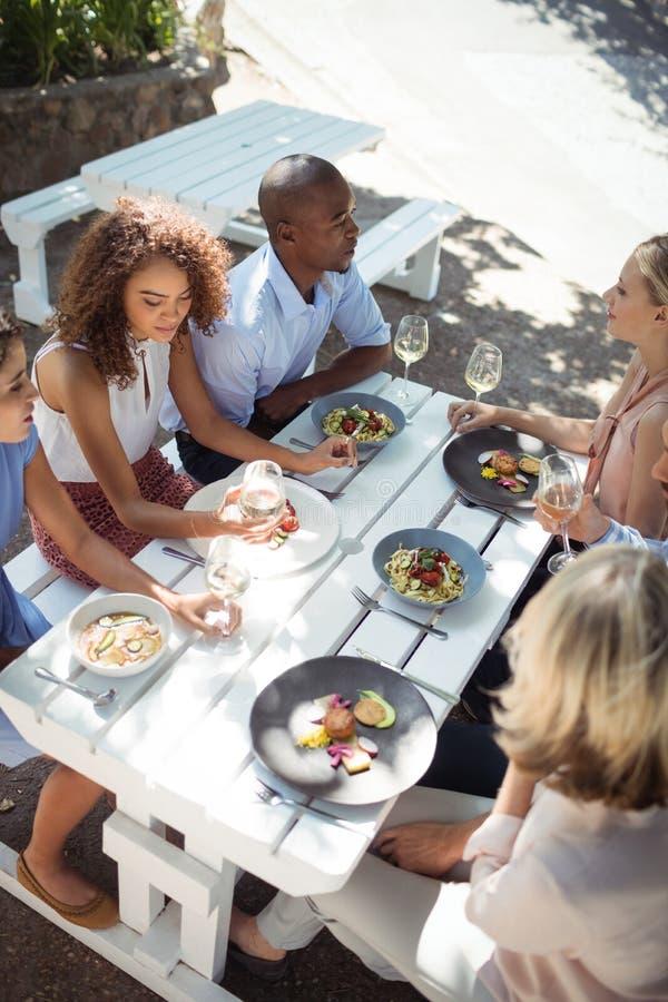 Glückliche Freunde, die auf einander beim Haben der Mahlzeit einwirken lizenzfreie stockfotografie