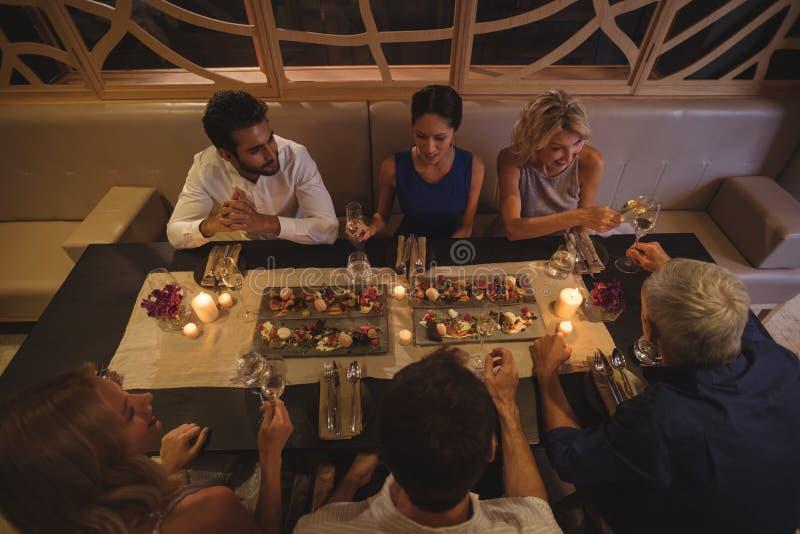 Glückliche Freunde, die auf einander beim Zu Abend essen einwirken stockfotografie