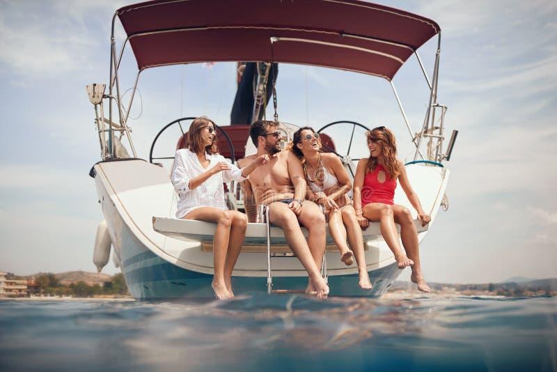 Glückliche Freunde, die auf einem Boot partying sind lizenzfreie stockfotografie