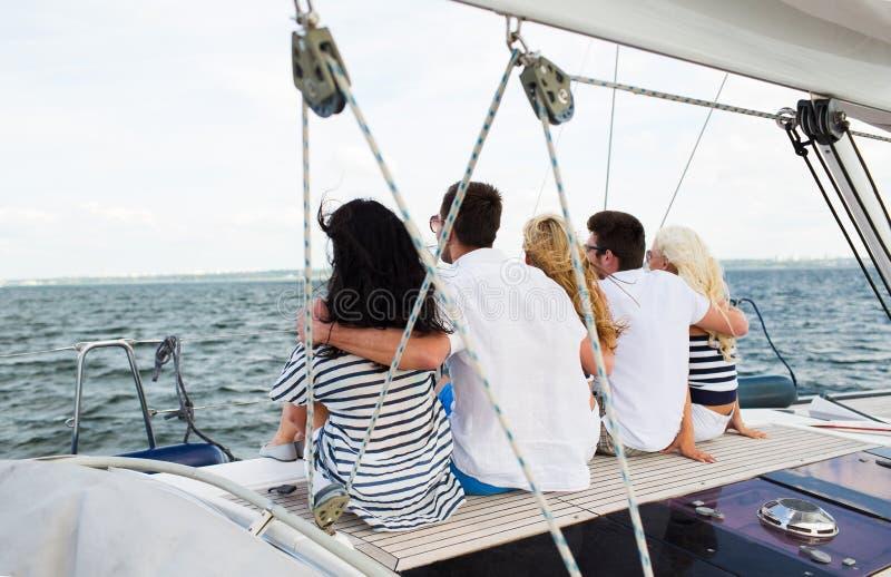 Glückliche Freunde, die auf Yachtplattform segeln und sitzen lizenzfreie stockfotografie