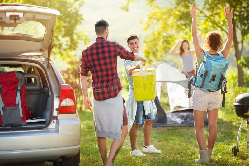 Glückliche Freunde, die Auto für Camping-Ausflug auspacken lizenzfreies stockbild