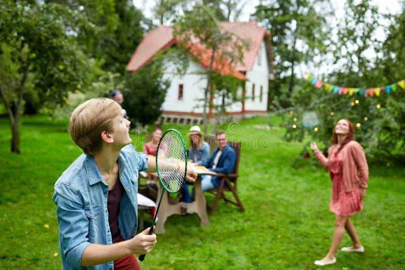 Glückliche Freunde, die Badminton am Sommergarten spielen stockfotos