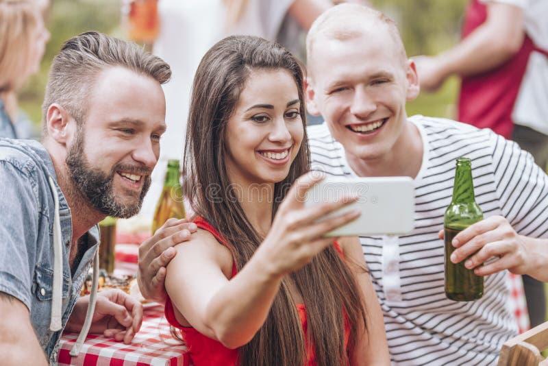 Glückliche Freunde, die Bier trinken und selfie während der Grillpartei nehmen stockfoto
