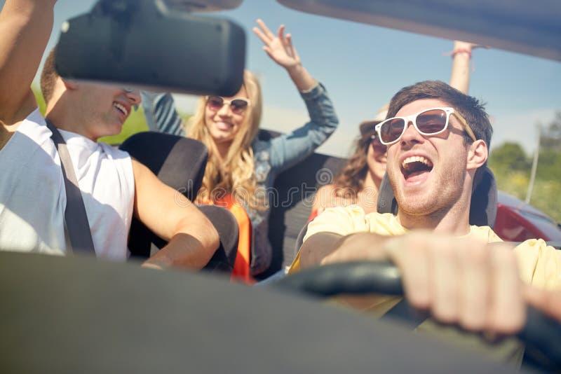 Glückliche Freunde, die in Cabrioletauto fahren stockfotografie