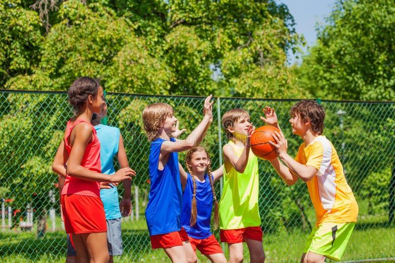 Glückliche Freunde, die draußen Basketballspiel spielen lizenzfreies stockfoto