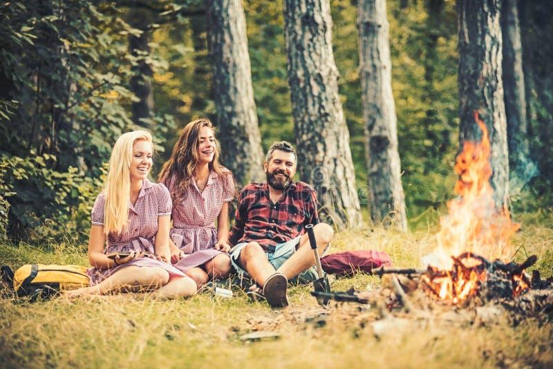 Glückliche Freunde, die draußen glätten genießen Junger Mann und zwei Frauen, die um Lagerfeuer sitzen Freunde, die in der Wildni lizenzfreies stockfoto