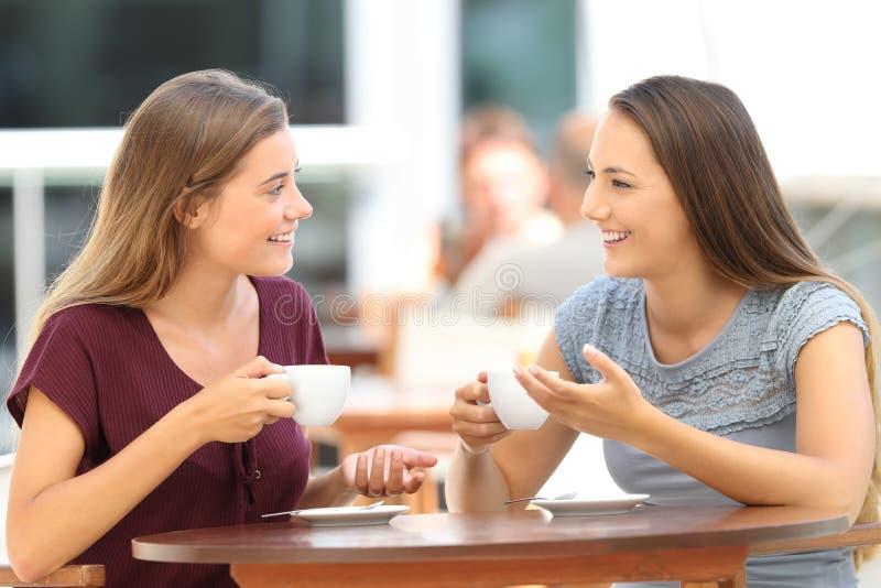 Glückliche Freunde, die ein Gespräch in einer Stange haben lizenzfreie stockfotografie